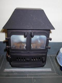 Gas burning stove to supplement solar powered under floor heating on cooler days