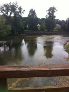 Río Sella visto desde el puente colgante de madera, situado delante del edificio.