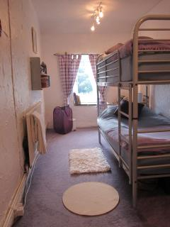 Second bedroom with bunk beds and cot.