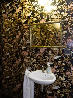 Quirky wallpaper in the ground floor half bath is part of the charm of the house.