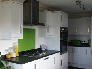 Well equipped modern sunny kitchen/diner with French doors opening onto a lawned area.