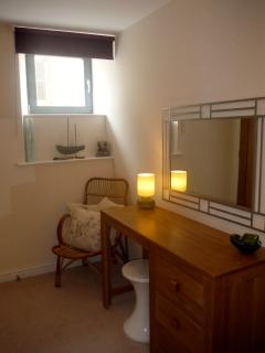 Bedroom is furnished with dressing table, drawers, fitted wardrobe and armchairs: lots of storage