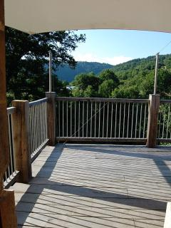 The large wooden terrace with superb views over the garden, swimming pool and down the Viaur Valley.