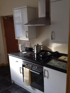 Kitchen units housing oven & ceramic hob with extractor fan above