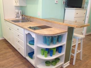 Cool kitchen area has seashell counter top and bar stools