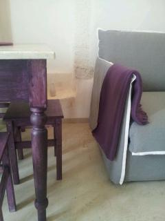 Living. Particolare tavolo, antica nicchia in pietra e divano letto
