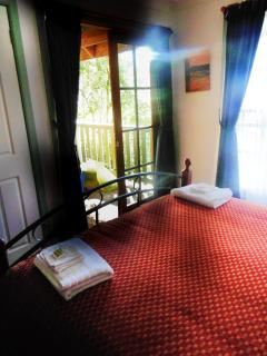 The comfortable queen bed leads on to the verandah and has a wide window to view the bush.