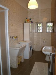 Bathroom with washing machine and shower