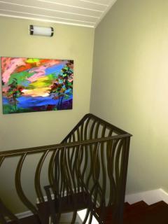 A Jonas Gerard original oil painting a a custom handrail highlight the stairwell.
