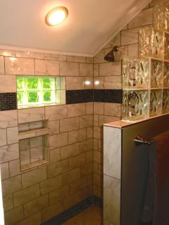 This bath has a large tiled walk in shower.