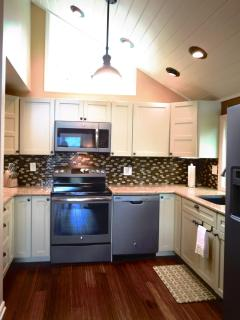 The kitchen has a quartz countertop, new Ge Slate appliances, and custom Martha Stewart cacinetry.