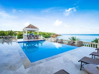 The Grand Master bedroom of this villa includes a private shower and large outdoor balcony overlooking the beach and sea. RIC SAN, Anguilla