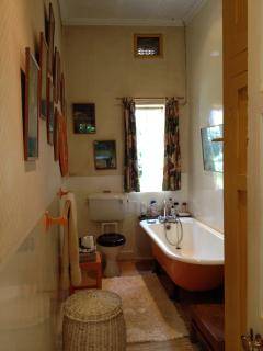the shared bathroom with claw foot bath and toilet, no basin