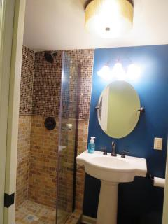 This bath has a pedestal sink and walk in shower with a frameless shower door.