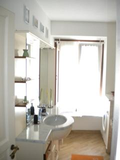 The bright bathroom, the full wall mirror, the floor of the washbasin in white Carrara marble