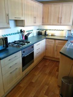 Fitted kitchen with gas hob, electric oven, washing machine and microwave.