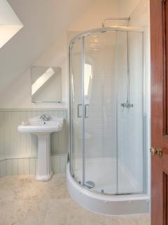 Twin-bedded bathroom with curved shower.