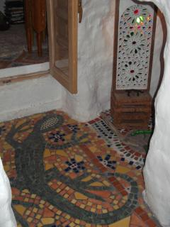 Mosaiced floor of passageway leading from double bedroom into feature cave.