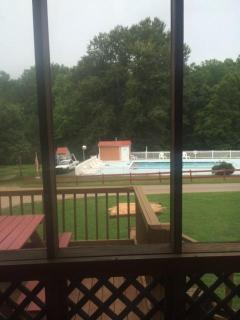 Looking outside the door of the cabin onto pool