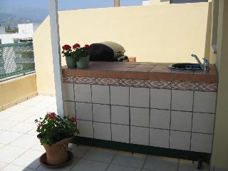 Utomhusköket med rinnande vatten och stor grill.