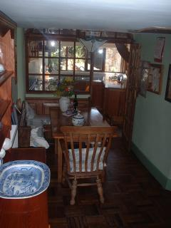 Dining room towards the kitchen, lovely pitch pine table, pews & dresser with willow pattern china.