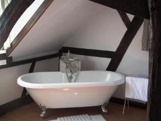Free standing bath within bedroom with bamboo modesty screen