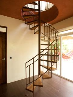 A spiral staircase leads to a very cozy twin bedroom on the third floor.