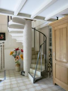 The Entrance foyer, with circular stairs that lead to a spacious loft configuration upstairs