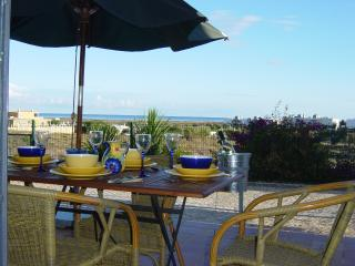 Sunny, suntrap patio with views across the garden to Meia Praia beach