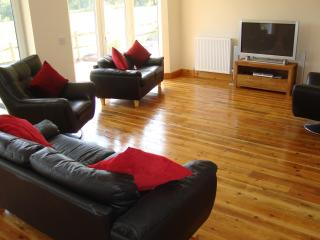 Large wooden floored lounge with country views and direct access to garden decking area.