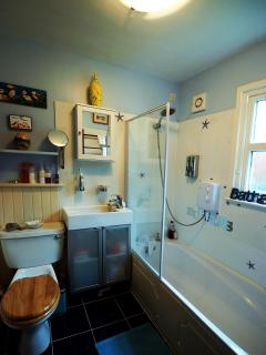 Bathroom with monsoon shower over bath