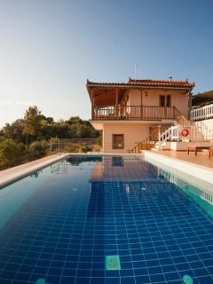 Pool and villa with marble steps into the pool and cushioned wooden pool furniture.