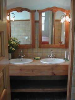 Baños con ducha, dos lavabos, wc y videt dentro de un dormitorio con cama de matrimonio.