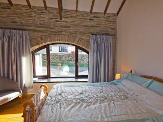 Second double bedroom with arched window in natural stone wall