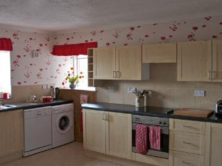 The kitchen includes a large dining table, dishwasher, washing machine, microwave and fridge freezer