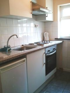 Kitchen with fridge, washing machine, full size oven and hob and microwave.