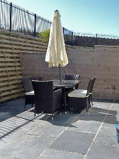 Rattan dining table and chairs seating 6 persons with parasol
