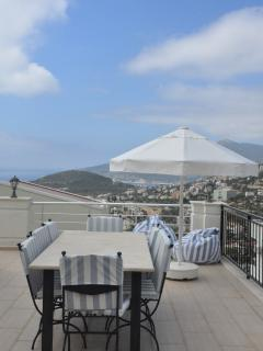 Large eight seater granite table for al fresco dining, 3 sun parasols can provide some shade