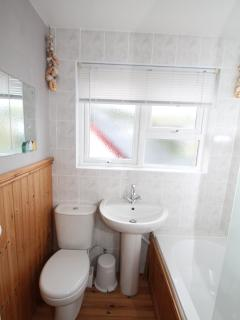 Modern white bathroom suite,    with over bath shower  +   shower screen