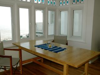 Dining table in the bay window, overlooking sandy Stone Bay