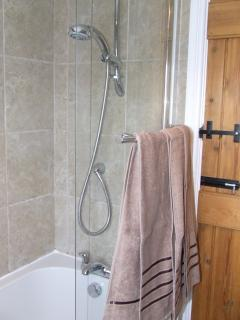 Power shower and bath, hot water on demand with heated floor mat.