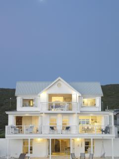 White clapperboard style house reflecting superior architecture.  Peaceful and private.