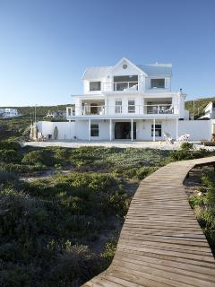 A private boardwalk separates the house from the beach.  Enjoy sundowners on the sand.
