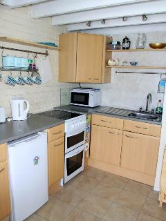 Small kitchenette area with double oven. grill, microwave, fridge and freezer