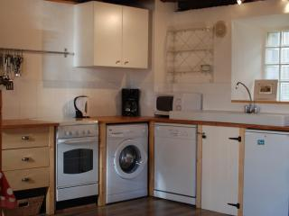 Kitchen with washing machine, dishwasher, fridge, microwave, coffee machine & kettle.