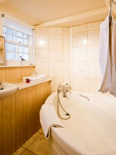 Bathroom with corner bath and hand-held shower attachment