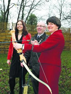 Tourism Minister, Arlene Foster, tries out her archery skills under the supervision of Caroline