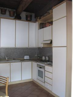Particular of the well equipped kitchen with 2 sinks, washing machine, dishwasher, oven, gas stove.