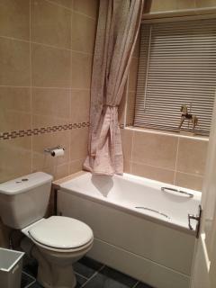 Fully tiled Bathroom with over-bath shower