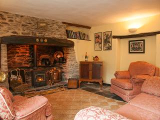 The sitting room has a huge stone inglenook fireplace and a log fire
